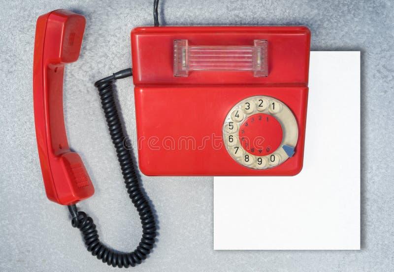 Telefone giratório antigo vermelho com a folha de papel vazia imagem de stock royalty free