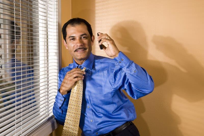 Telefone latino-americano de meia idade da terra arrendada do homem de negócios foto de stock royalty free