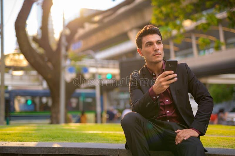 Telefone latino-americano pensativo novo da terra arrendada do homem de negócios e assento com natureza na cidade fotografia de stock