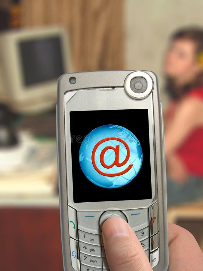 Telefone móvel à disposicão, @ e terra no indicador fotografia de stock