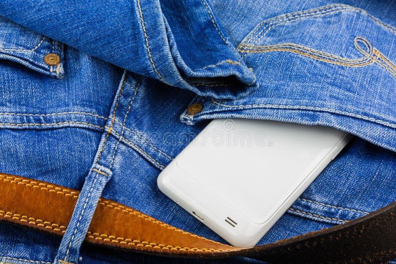 Telefone móvel no bolso traseiro da calças de ganga imagem de stock