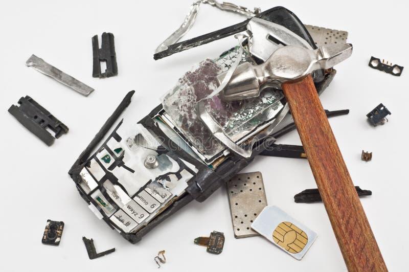Telefone móvel quebrado com um martelo fotografia de stock