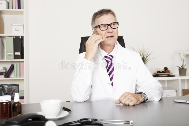 Telefone masculino de Calling Client Through do médico foto de stock royalty free