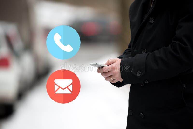 Telefone ou correio Homem de negócios que guarda um móbil do smartphone, colado no tráfego em um dia de inverno frio da neve Home foto de stock