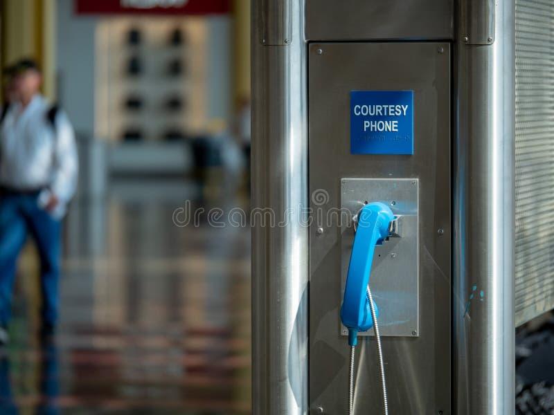 Telefone público azul da cortesia do uso situado em um aeroporto fotos de stock royalty free