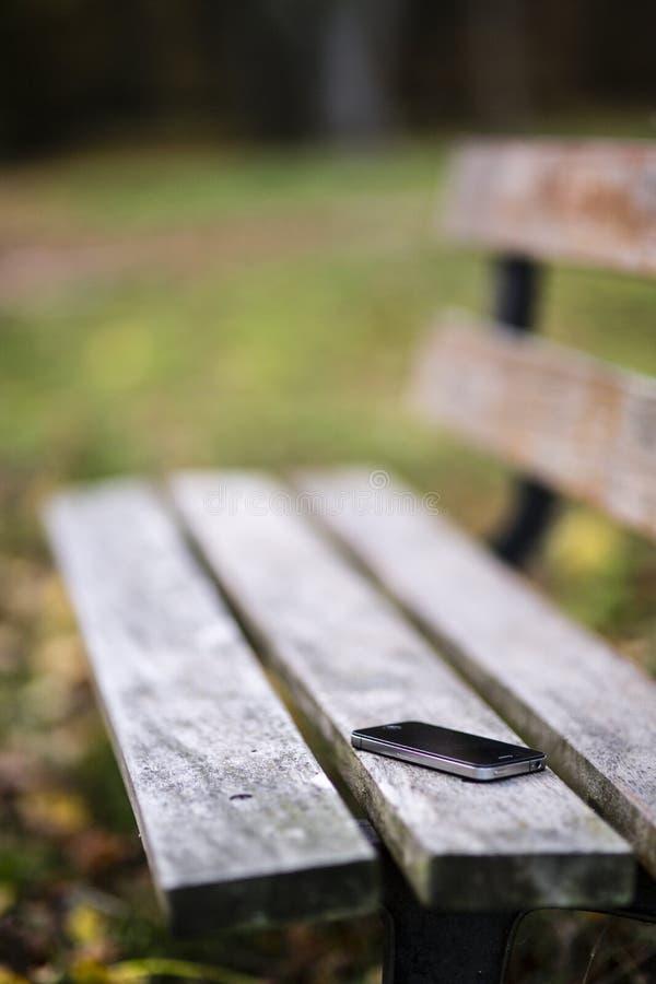 Telefone perdido no banco fotografia de stock