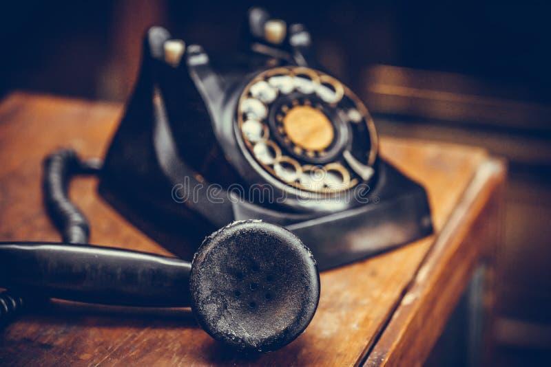 Telefone preto do vintage no fundo de madeira velho da tabela fotografia de stock royalty free