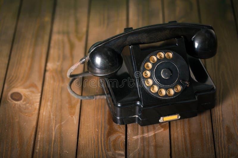 Telefone preto retro no fundo de madeira imagem de stock royalty free