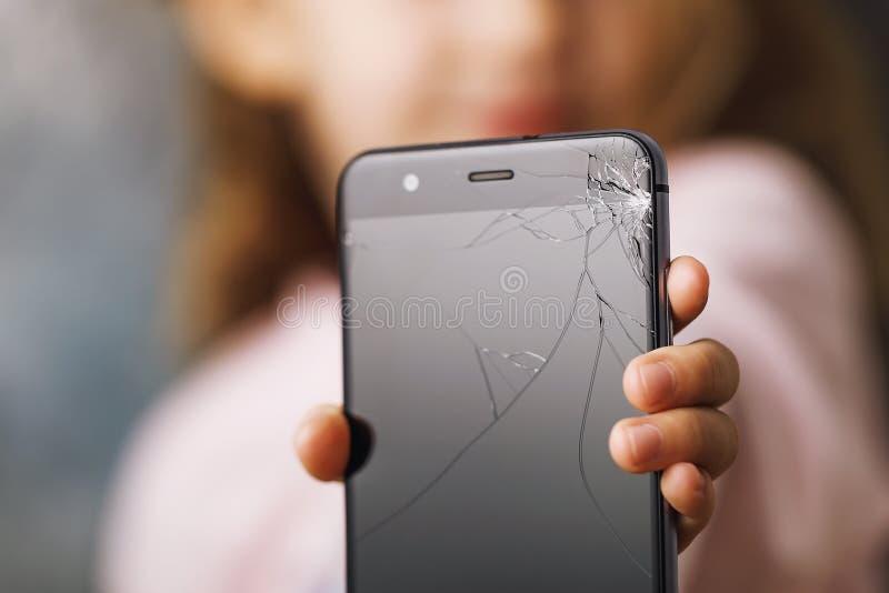 Telefone quebrado nas mãos da criança pequena imagens de stock royalty free