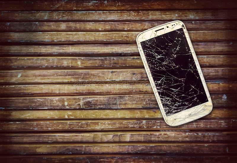 Telefone quebrado no banco de madeira fotos de stock