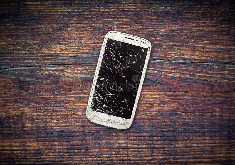 Telefone quebrado no banco de madeira fotografia de stock