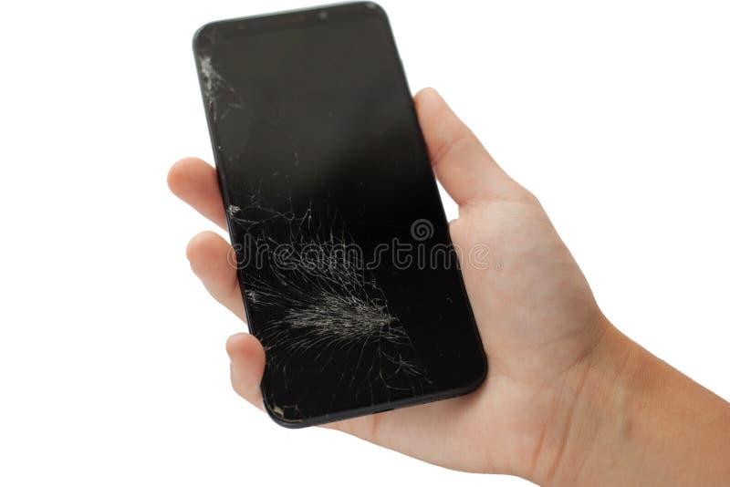 Telefone quebrado preto à disposição em isolado rachado da tela do écran sensível do fundo branco imagens de stock royalty free