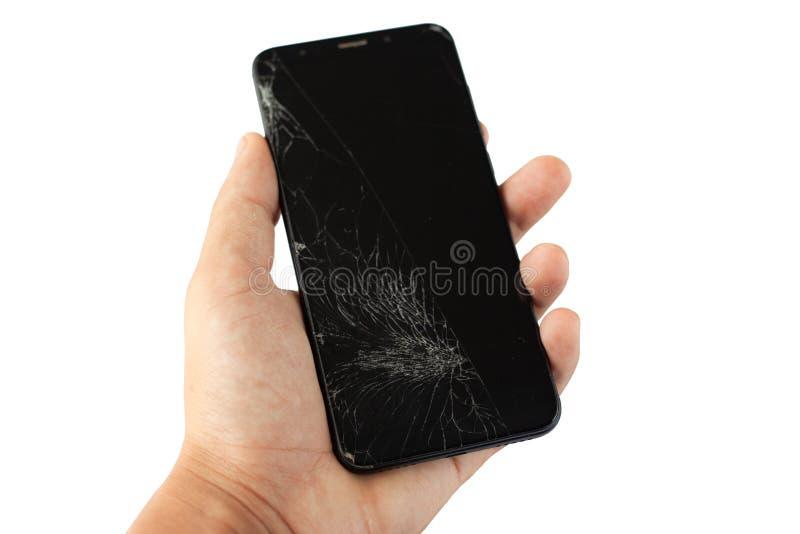 Telefone quebrado preto à disposição em isolado rachado da tela do écran sensível do fundo branco foto de stock