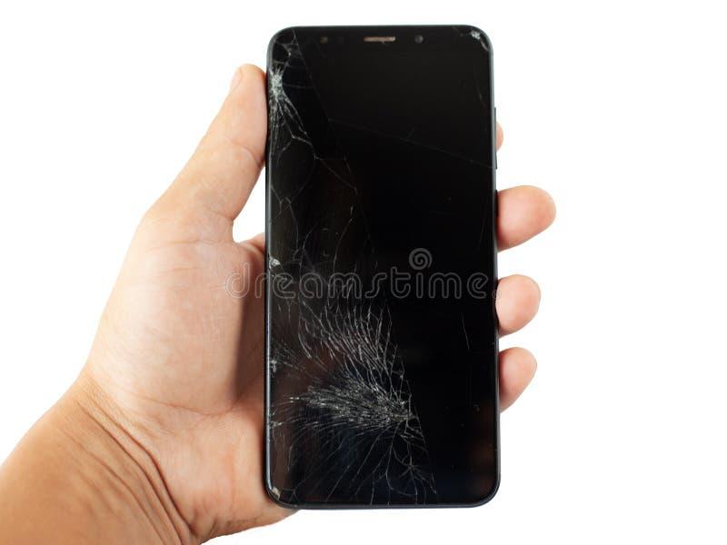 Telefone quebrado preto à disposição em isolado rachado da tela do écran sensível do fundo branco imagem de stock royalty free