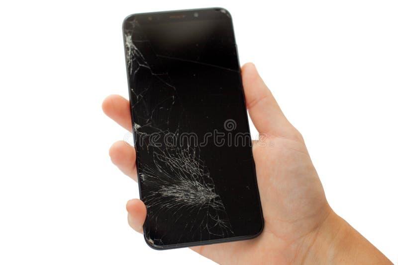 Telefone quebrado preto à disposição em isolado rachado da tela do écran sensível do fundo branco fotografia de stock royalty free