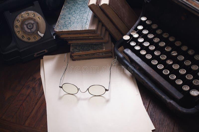Telefone retro velho com máquina de escrever do vintage e uma folha de papel vazia na placa de madeira imagens de stock