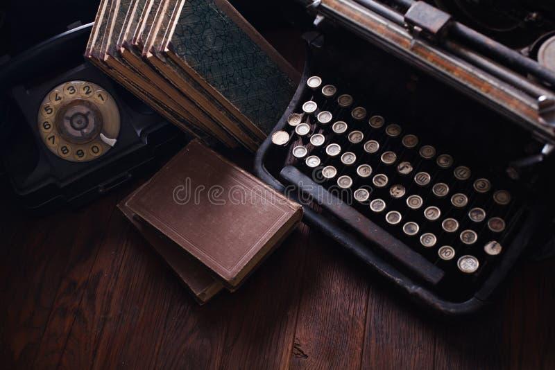 Telefone retro velho com máquina de escrever e livros do vintage na placa de madeira fotografia de stock