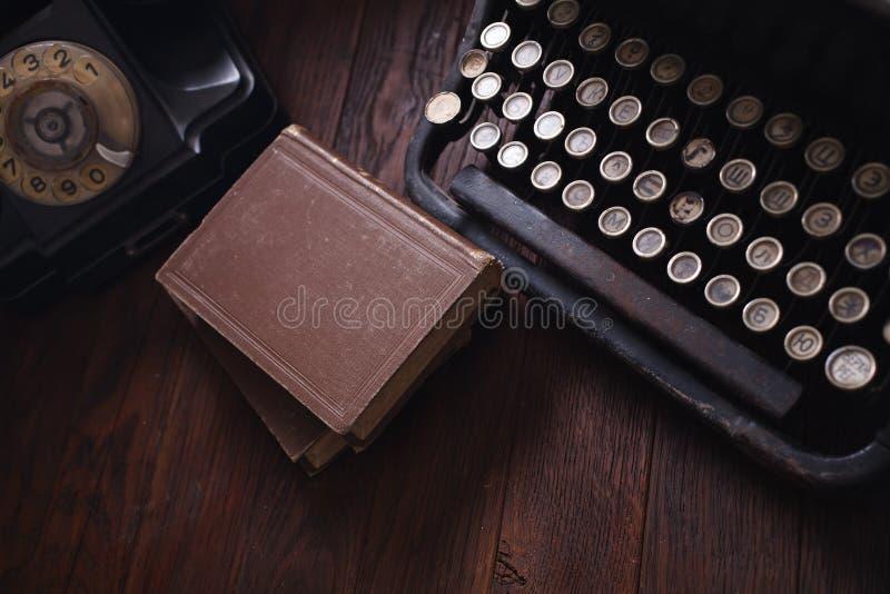 Telefone retro velho com máquina de escrever e livros do vintage na placa de madeira foto de stock royalty free