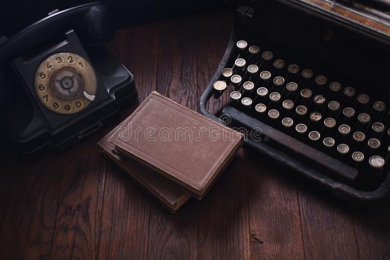 Telefone retro velho com máquina de escrever e livros do vintage na placa de madeira fotografia de stock royalty free
