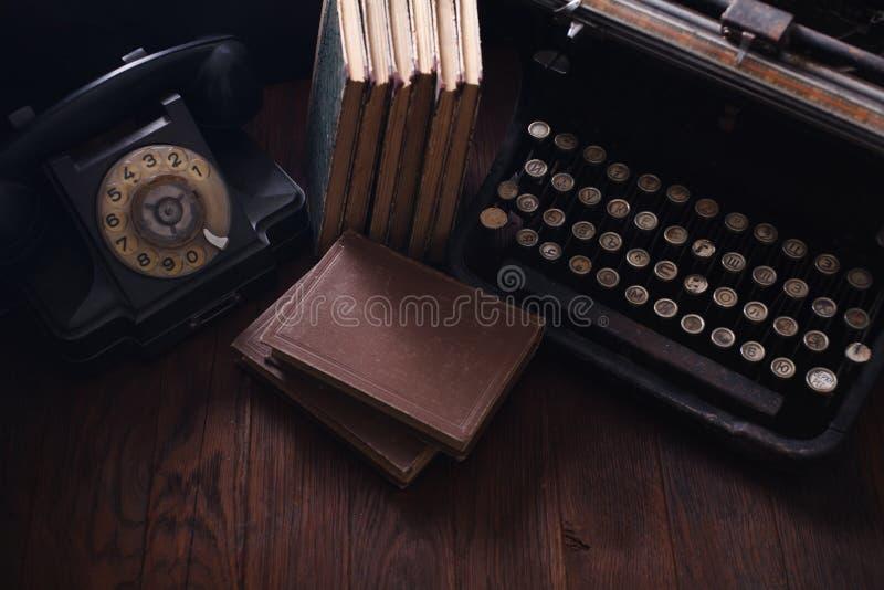 Telefone retro velho com máquina de escrever e livros do vintage na placa de madeira imagens de stock