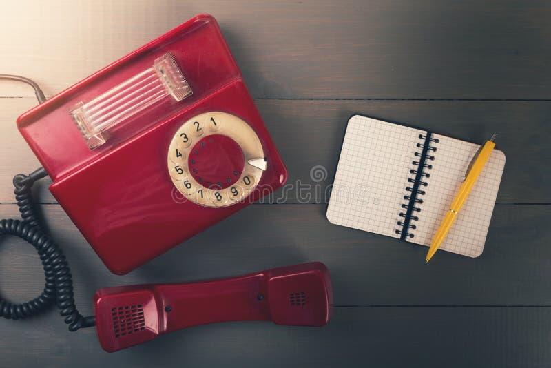 telefone retro velho com o caderno do contato na tabela de madeira Vista superior foto de stock