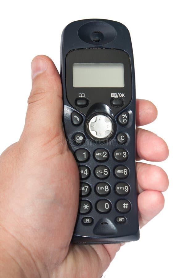 Telefone sem fios preto na mão no fundo branco fotografia de stock