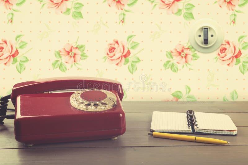Telefone velho com o caderno na tabela na sala do vintage fotos de stock