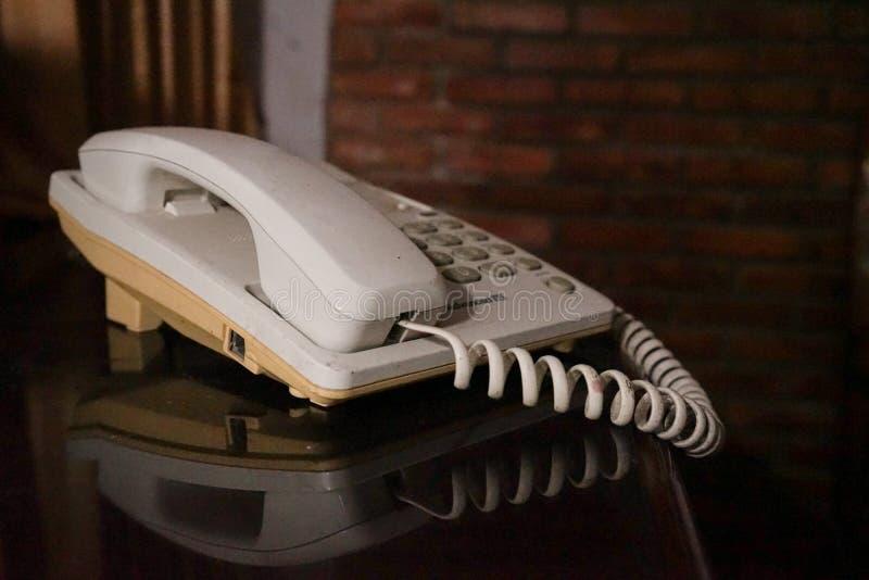 Telefone velho na casa da parede de tijolo imagens de stock