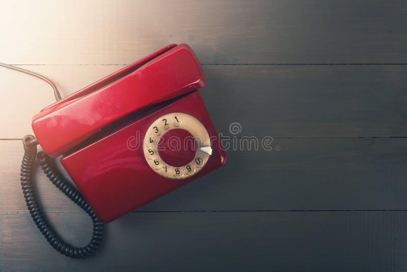 Telefone vermelho velho na tabela de madeira com espaço da cópia fotos de stock royalty free