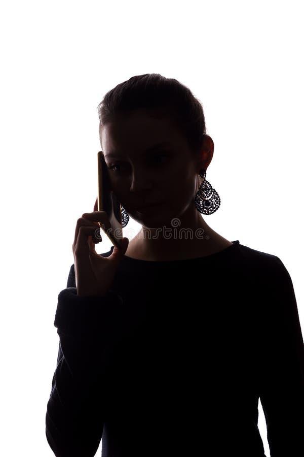 Telefonema da jovem mulher - silhueta foto de stock