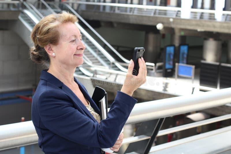 Telefonen för den hållande mobilen för affärskvinnan förbinder den smarta med wifi på den flygplats- eller drev-, gångtunnel- ell royaltyfri bild