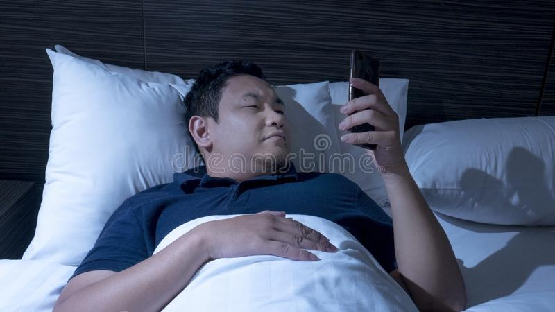Telefonen missbrukade, mannen som använder den smarta telefonen på säng på midnatt royaltyfri foto