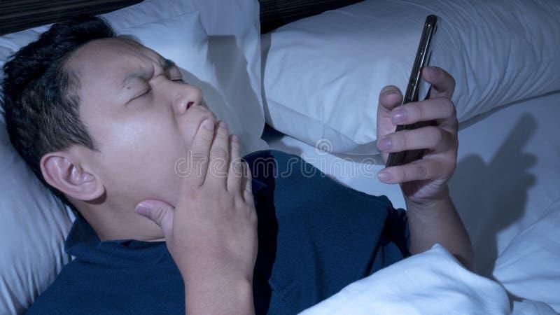 Telefonen missbrukade, mannen som använder den smarta telefonen på säng på midnatt royaltyfri bild
