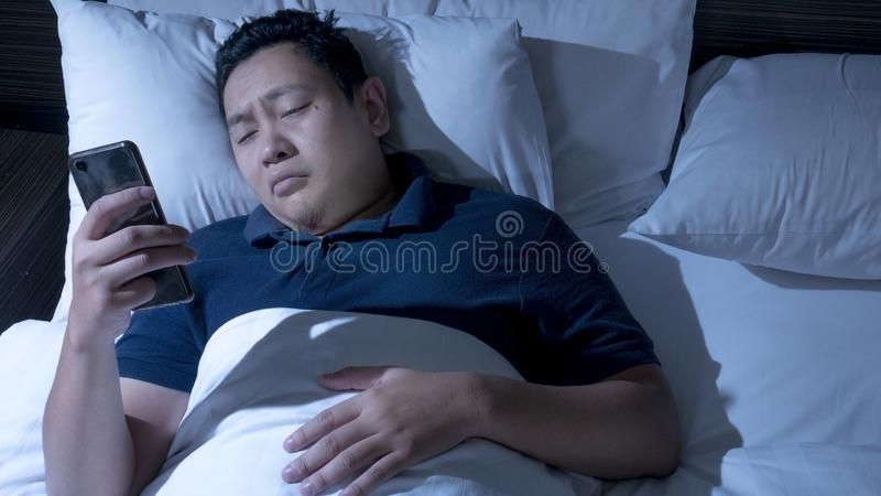 Telefonen missbrukade, mannen som använder den smarta telefonen på säng på midnatt arkivfoto