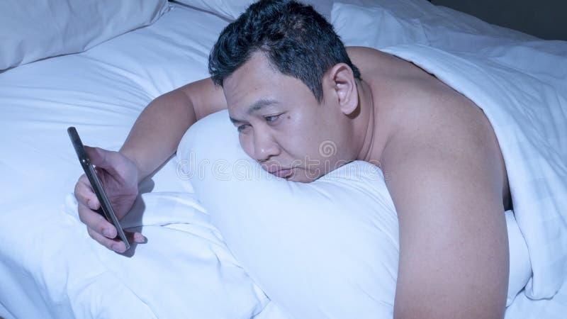 Telefonen missbrukade, mannen som använder den smarta telefonen på säng på midnatt fotografering för bildbyråer