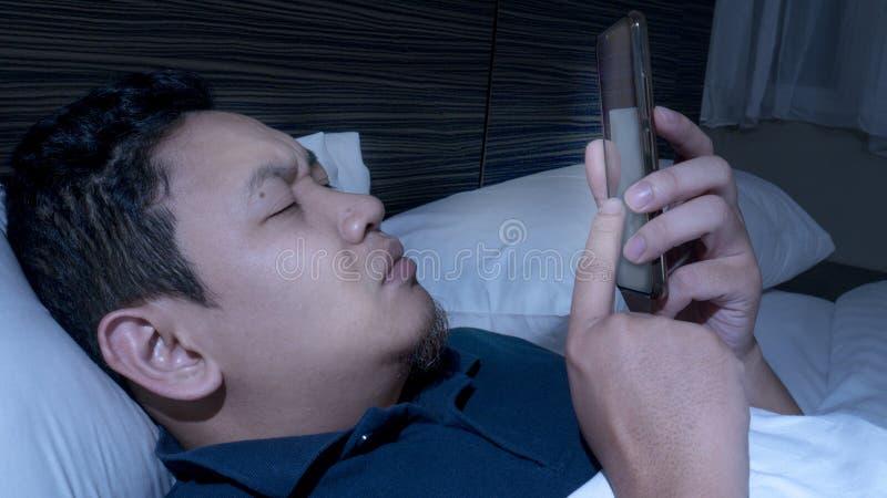 Telefonen missbrukade, mannen som anv?nder den smarta telefonen p? s?ng p? midnatt royaltyfri bild