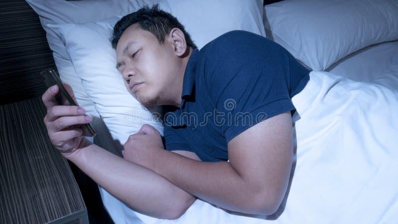 Telefonen missbrukade, mannen som anv?nder den smarta telefonen p? s?ng p? midnatt royaltyfria bilder