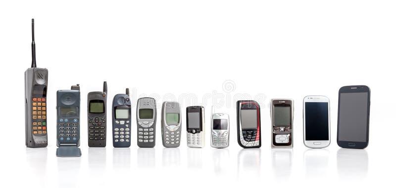 Telefones celulares velhos do passado ao presente no fundo branco fotografia de stock