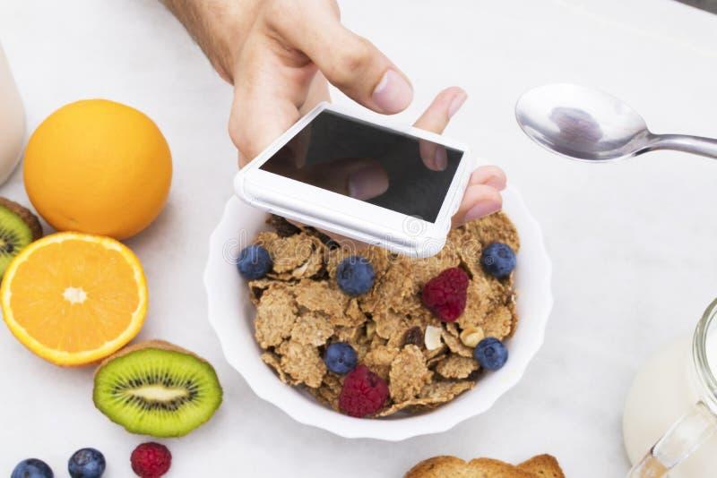 Telefonhänder på frukosten royaltyfri bild