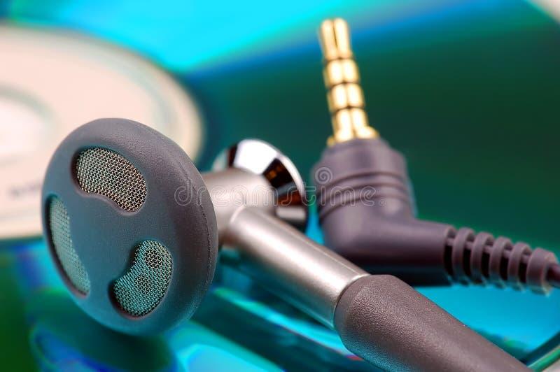 Telefoni dell'orecchio e spina di Jack su priorità bassa cd colorata immagini stock
