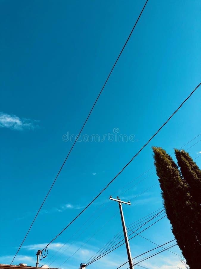 Telefoniczni druty przeciw jasnemu niebieskiemu niebu zdjęcia royalty free