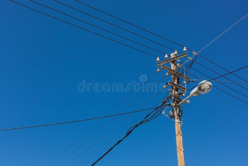 Telefoniczny lampowy słup z elektrycznymi drutami przeciw niebieskiemu niebu obrazy stock