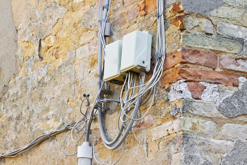 Telefonkabel ungefähr zusammengebaut mit Plastikanschlusskasten gegen eine alte Gipswand lizenzfreie stockfotos