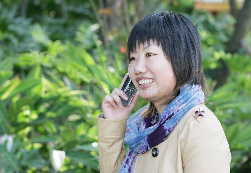 telefono asiatico delle cellule usando donna fotografia stock