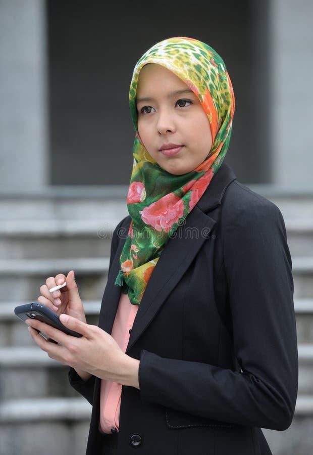 Ragazza della sciarpa con il telefono astuto immagine stock