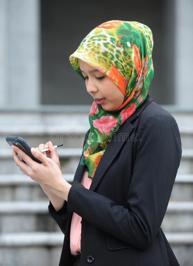 Ragazza della sciarpa con il telefono astuto fotografia stock