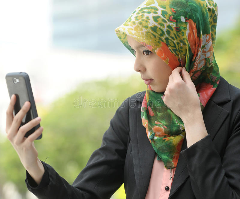 Ragazza della sciarpa che per mezzo del telefono astuto immagini stock libere da diritti