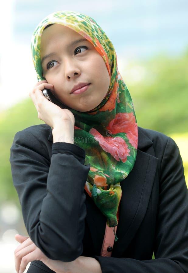 Ragazza della sciarpa che per mezzo del telefono astuto immagine stock