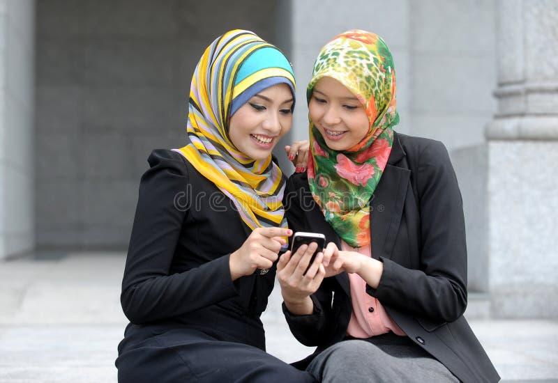 Una ragazza di due sciarpe che per mezzo del telefono astuto immagini stock libere da diritti
