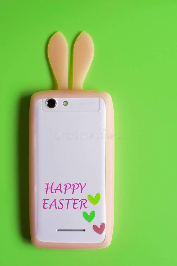Telefono bianco con le orecchie arancione-chiaro del coniglietto immagine stock